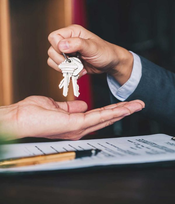 green-house-estate-agent-giving-house-keys-to-woman-and-sign-agreement-in-office